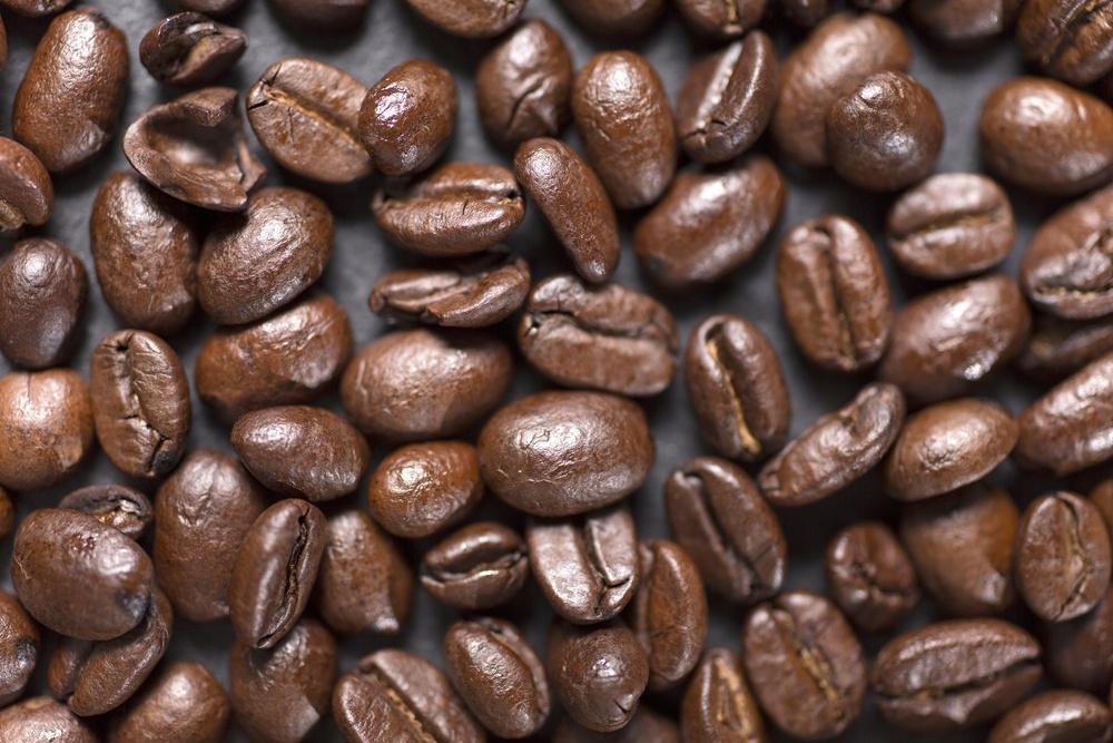 Fresh roasted coffee beans on a black slate surface.jpeg