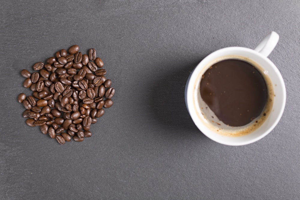 Still life of fresh roasted coffee beans with a white mug on a black slate surface-1.jpeg